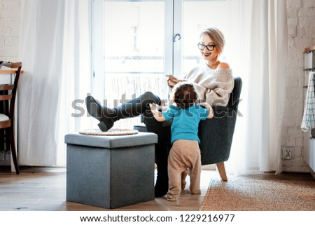 Young mother with mobile phone sitting in armchair and little toddler boy stay next to her on a flloor. Home interior decoration #1229216977