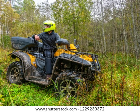 A man travels on ATV. Yellow quad bike. Off-road travel. The man in the helmet. Yellow ATV. #1229230372