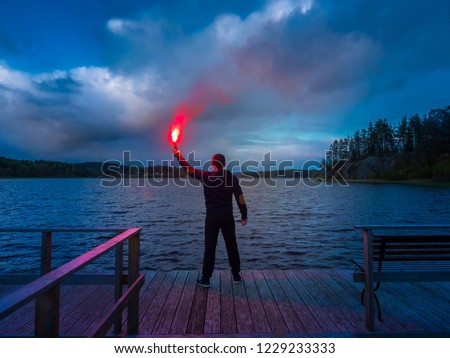Signal for help. A man signals a torch in his hand. SOS. A man holds a torch in his hand. Royalty-Free Stock Photo #1229233333