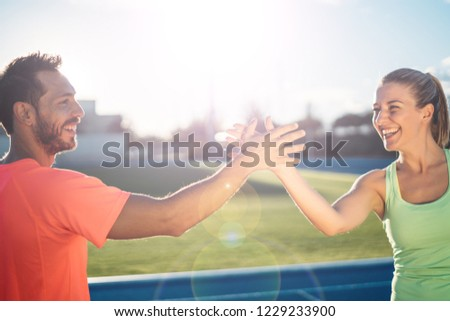 Couple of Runners giving high five to each other after a training session. Athletes celebrating success after a race. #1229233900