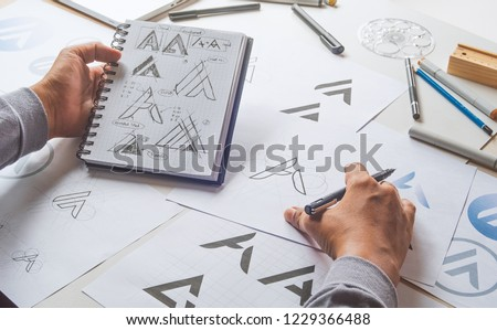 Graphic designer drawing sketch design creative Ideas draft Logo product trademark label brand artwork. Graphic designer studio Concept. #1229366488