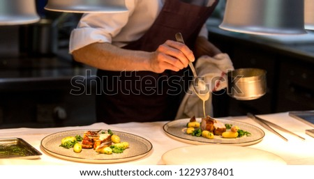 Chef preparing a plate made of meat and vegetables. The chef is pouring sauce on two plates. #1229378401