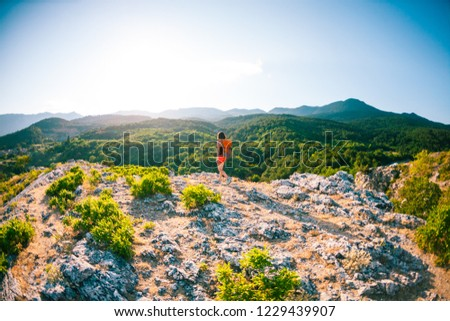 Girl at the top of the mountain. A woman with a backpack is standing on a rock. Climb to the top. Travel to picturesque places. Tourist against the sky and the sea. The brunette looks at the horizon. #1229439907