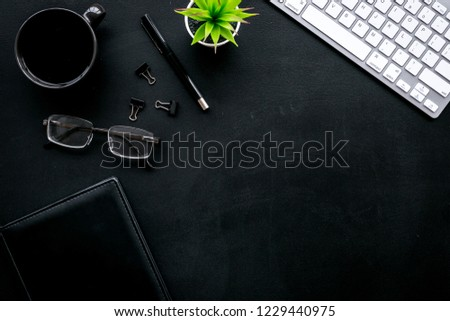 Flat lay of office desk, office workplace. Keyboard and glasses near coffee and stationery on black background top view space for text #1229440975
