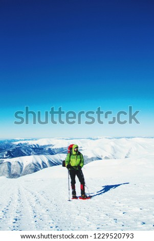 Winter hiking in the mountains with a backpack in snowshoes. #1229520793