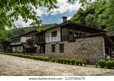 Old typical traditional Bulgarian house with white walls, wooden windows, architecture from Bulgarian National Revival period of 19th century. Bulgaria, Gabrovo, Open Air Ethnographic Museum Etar. #1229586670