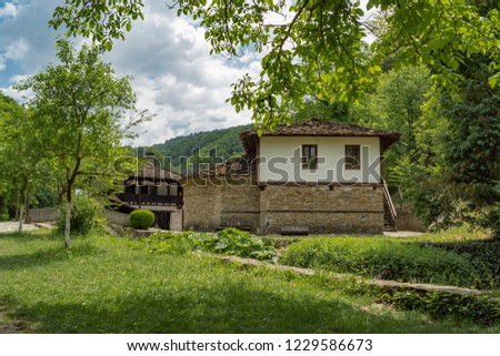 Old typical traditional Bulgarian house with white walls, wooden windows, architecture from Bulgarian National Revival period of 19th century. Bulgaria, Gabrovo, Open Air Ethnographic Museum Etar. #1229586673
