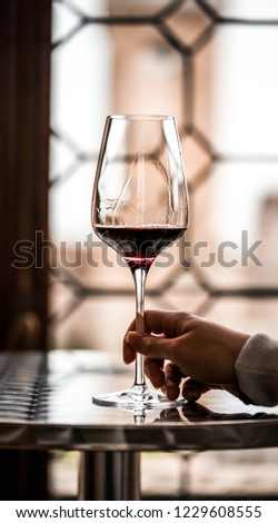 Glass of red wine with luxury background. Woman hand holding the glass. #1229608555