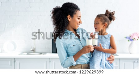 smiling african american mother and daughter holding glasses of milk in kitchen and looking at each other Royalty-Free Stock Photo #1229629399