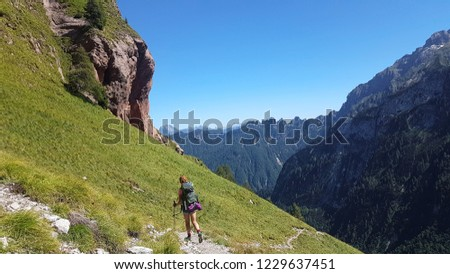 Hiker with backpack walking a grass trail on top of a mountain and enjoying valley view during sunny trip in the alps #1229637451