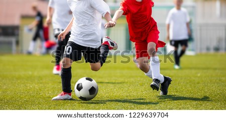 Two Young Boys in Soccer Sportswear Running and Kicking Ball on the Field. Low Angle Image of Youth Football Competition with Blurred Background #1229639704