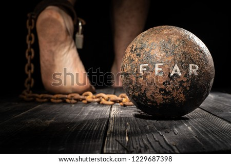 Fear is ball on the leg. Concept of fear. Royalty-Free Stock Photo #1229687398