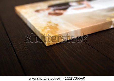 Sample of photography with gallery stretch on a wooden frame. Printed wedding photo on canvas lying on wooden table. Lateral side closeup. Selective focus