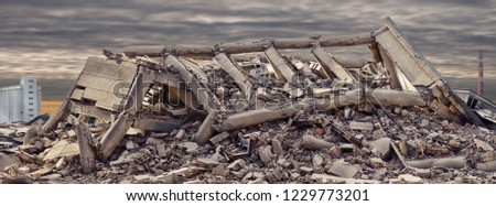 Collapsed concrete industrial building with dramatic sky and factory chimney and another concrete building in background. Disaster scene full of debris, dust and damaged house. #1229773201