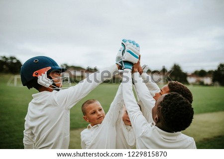 Group of young cricketers doing a high five