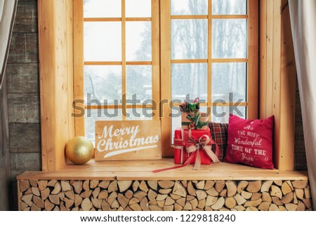 Cozy and frost winter day: christmas decoration on wood windowsill and snow landscape from outside. #1229818240