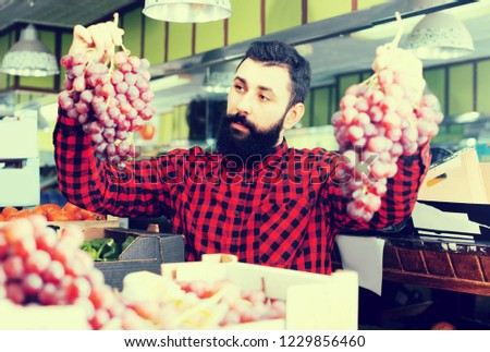 Positive man seller choosing  grapes in grocery store #1229856460