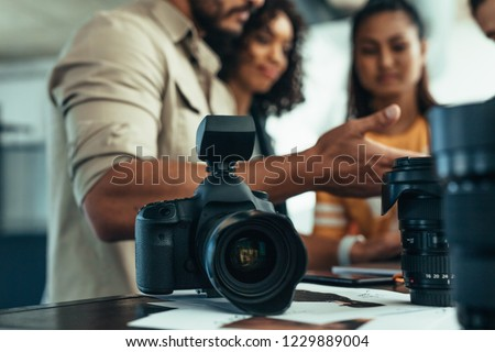 Professional DSLR camera and lens on the table with team of photographers discussing in the background. Photographer talking to his team during a photo shoot. #1229889004