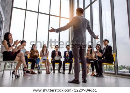 Male and female creative coworker listening explanation of male train manager during workshop sitting in office.Skilled couch conducting business seminar with professionals.Advertising area Royalty-Free Stock Photo #1229904661