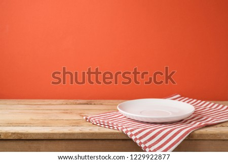Empty white plate with tablecloth on wooden table over red wall  background #1229922877