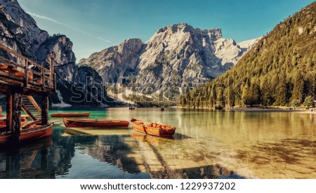 Awesome Sunny nature landscape. Impressively beautiful lake Braies  at sunrise. best popular location for photographer in Dolomites Alps. view on Impressive lake with turquoise water and boats.  #1229937202