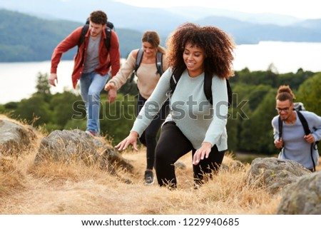 A multi ethnic group of young adult young adult friends smiling while climbing to a mountain summit, close up #1229940685