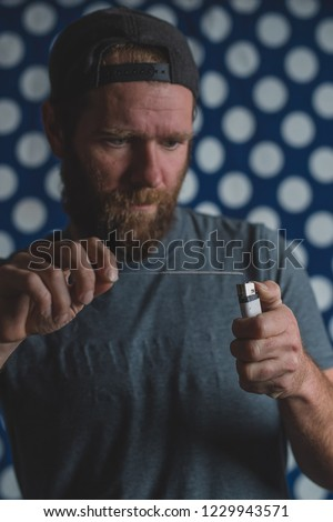 Hipster looking man with beard trying to light up a straw with a lighter. Man using a lighter to ignite a firecracker. #1229943571