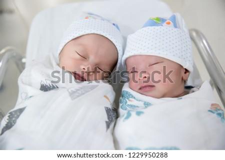 Newborn twins sleeping.Newborn Babies Twins Sleep in Bed.Lovely sleep of the newborns babies on the bed.