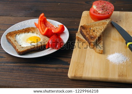 Fried eggs in bread on a torch, tomato and pepper on the table. #1229966218