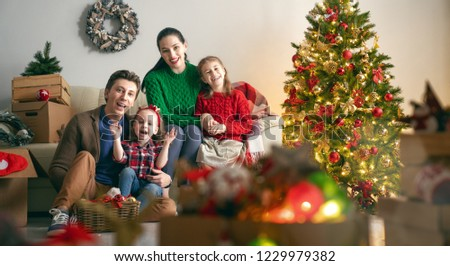 Merry Christmas and Happy Holidays!  Mother, father and children decorate the tree in room. Loving family indoors. #1229979382