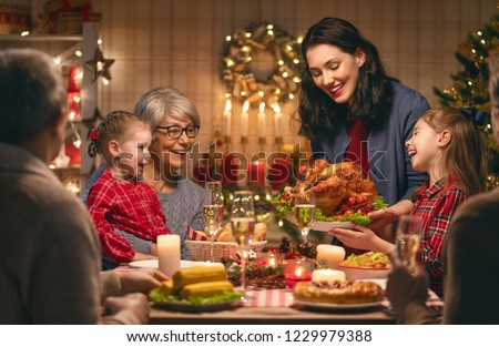 Merry Christmas! Happy family are having dinner at home. Celebration holiday and togetherness near tree. #1229979388