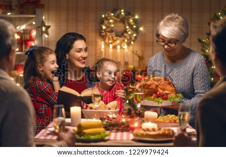 Merry Christmas! Happy family are having dinner at home. Celebration holiday and togetherness near tree. #1229979424