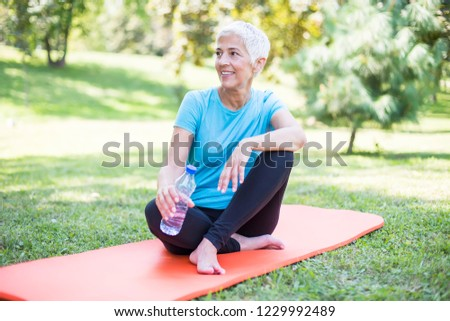 Senior sportive woman sitting on mat outside and resting after workout #1229992489