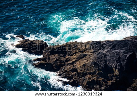 rocks in the sea with the waves crushing on them #1230019324