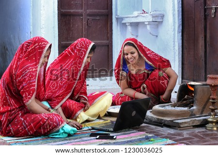 Three traditional Indian young married women working in traditional kitchen on laptop. Using technology in rural households. Women cook food and learn technology. Rural women using Laptop.  Royalty-Free Stock Photo #1230036025