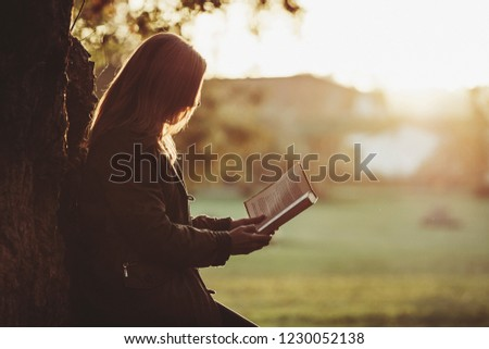 Woman reading a book in the park #1230052138