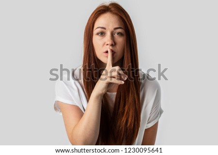 Attractive redhead girl with shhh gesture, asking for silence or to be quiet, isolated on gray background #1230095641