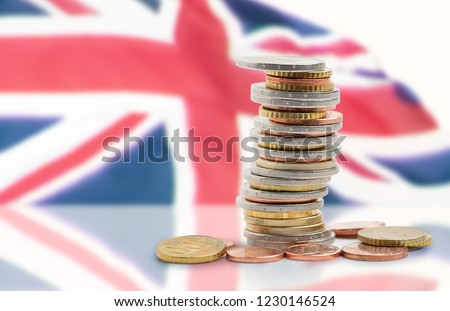Coins stacked on each other in different positions with United kingdom flag #1230146524