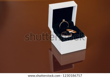 Three beautiful golden wedding rings in the box on the wooden table. Close up #1230186757