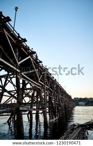 Beautiful sunset scene at old an long wooden bridge Asian wooden bridge Kanchanaburi province, Thailand #1230190471