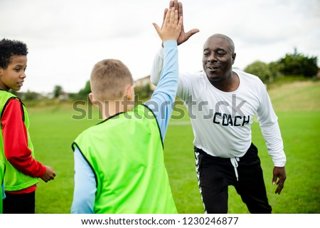 Football coach doing a high five with his student Royalty-Free Stock Photo #1230246877