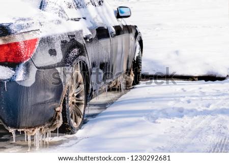 Freezing rain ice coated car.Bad driving weather in freezing rain.Black vehicle car covered in freezing rain #1230292681