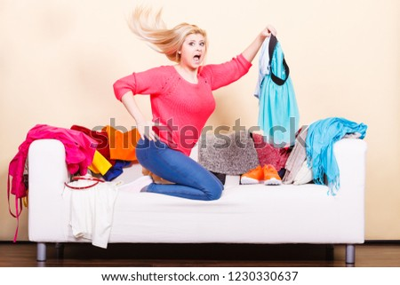 Style dilemmas concept. Shocked woman does not know what to wear sitting on messy couch with piles of clothes and looking through clothing. #1230330637