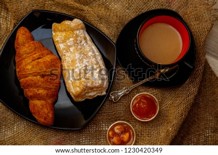 Two croissants on a plate and a cup of coffee with milk on a textural canvas background. #1230420349