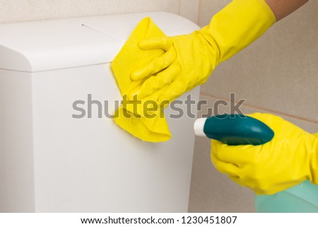 Person wearing gloves cleaning toilet with yellow cloth and spray as bathroom cleaning concept #1230451807