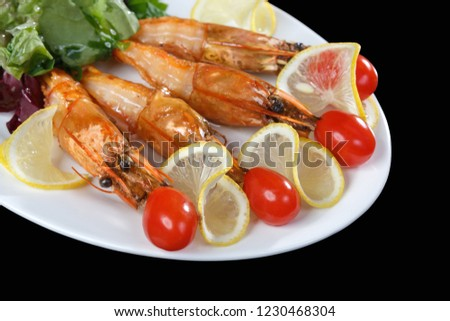 Shrimps, tomatoes and lemon are beautifully laid out on a dish on a black background. Freshly prepared shrimp #1230468304