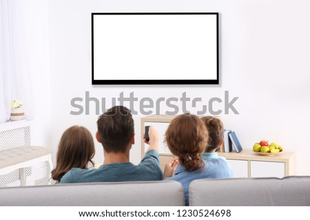 Family with remote control sitting on couch and watching TV at home, space for design on screen. Leisure and entertainment #1230524698