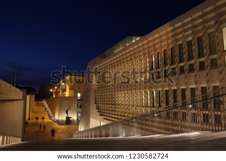 Evening strollers walk past the City Gate and Parliament buildings at the entrance to Valletta. Project was designed by architect Renzo Piano and built between 2011-2015 #1230582724