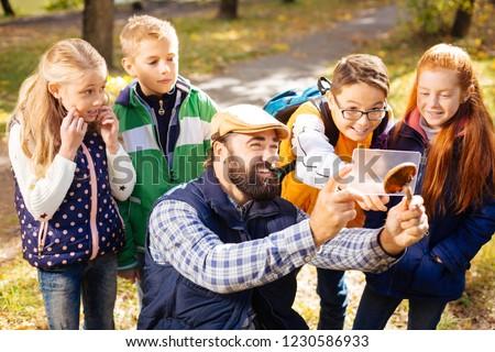 Team of explorers. Joyful cute children standing behind their teacher while looking at him taking photos #1230586933
