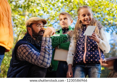 Biology lesson. Nice cheerful girl standing with her teacher while having an outdoor biology lesson #1230586966
